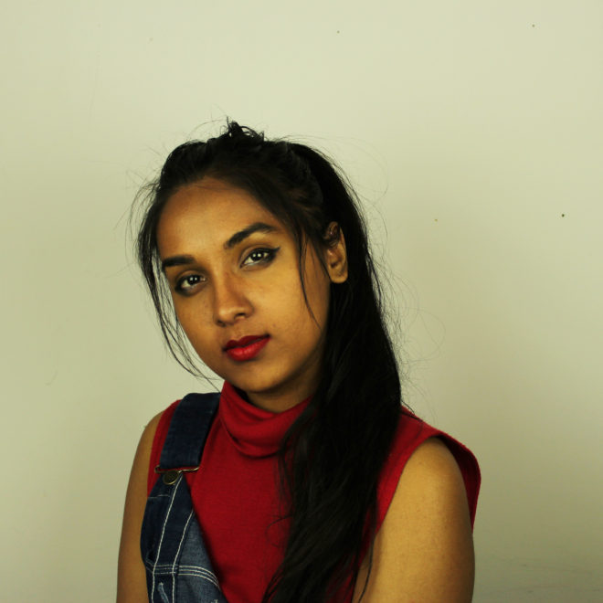 a picture of a young south asian woman smizing