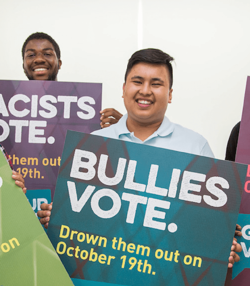 four young people holding signs, smiling at the camera