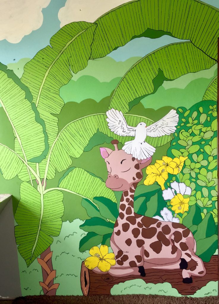 In the bottom right corner is a giraffe sitting on top of a log. Flying above the giraffe is a white dove. The background is made up of white and yellow flowers, embedded within greenery from trees and bushes.